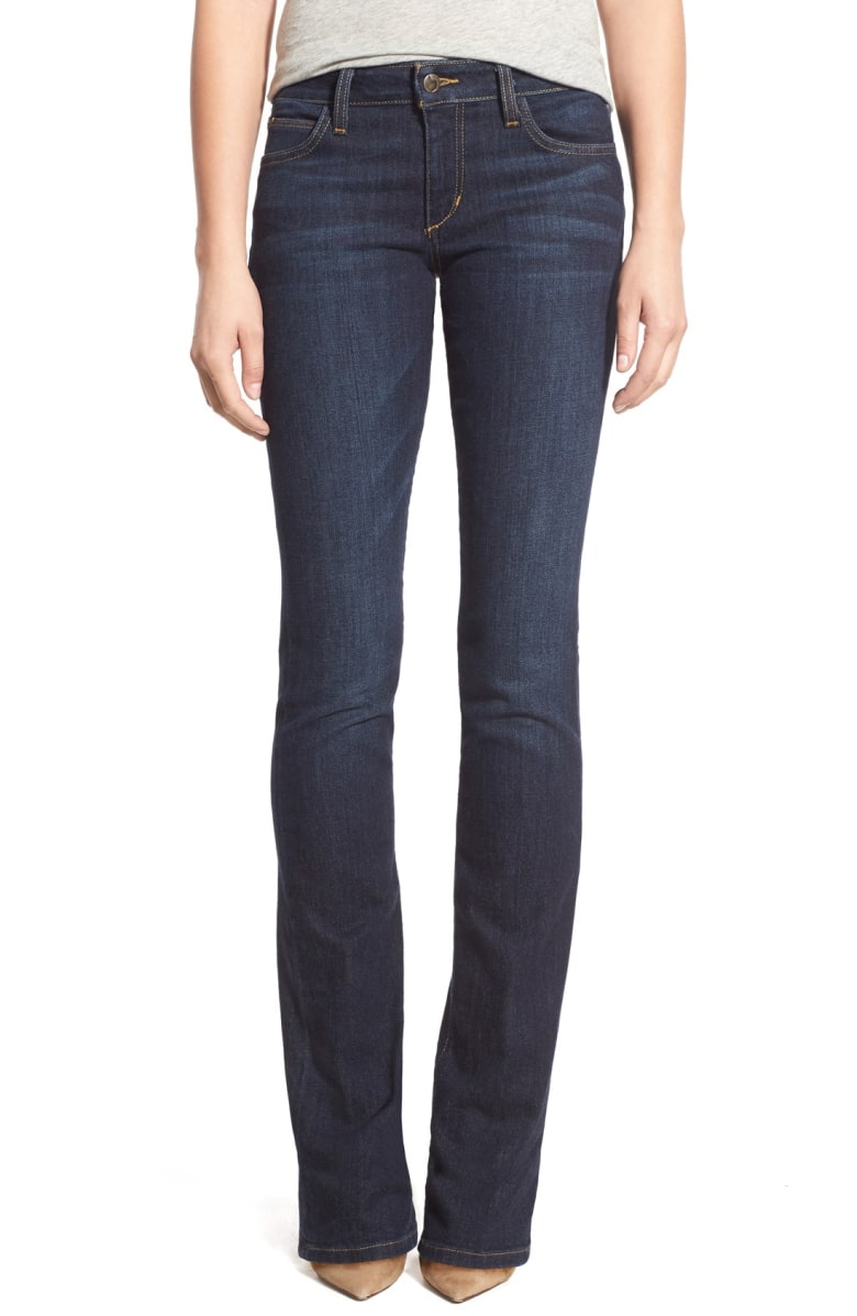 Boot cut jeans cover neutral high heel shoes