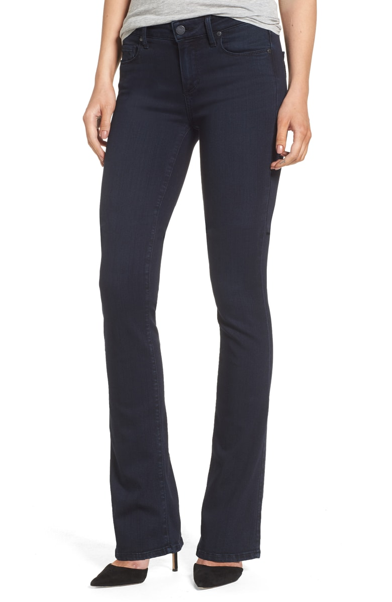 Dark high rise bootcut style jeans blend in with similar color shoe