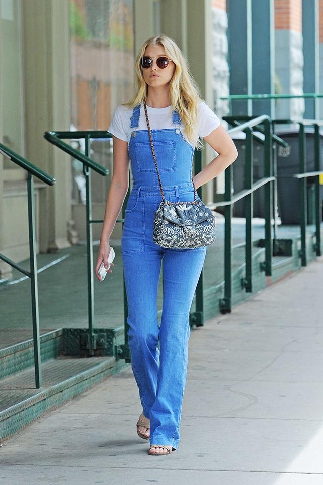 Elsa Hosk wears denim overalls, clean simple denim outfit